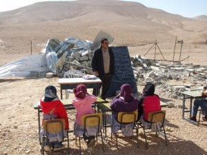 Chidren study in front of their classroom - demolished by the Israeli occupation forces.